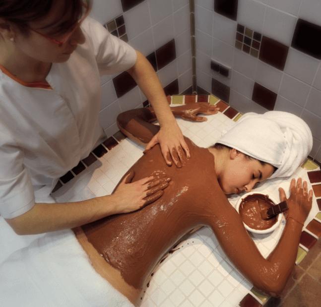 A Imagem Ilustra Uma Mulher Realizando Uma Sessão De Chocolaterapia Através De Massagens