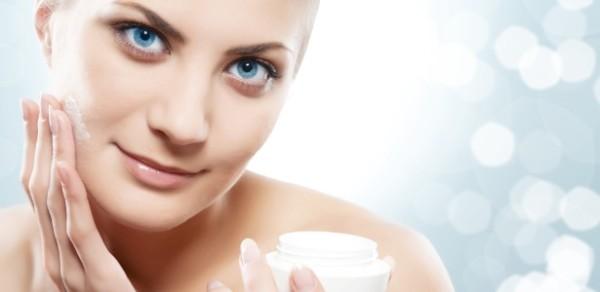 mulher aplica creme facial hidratante